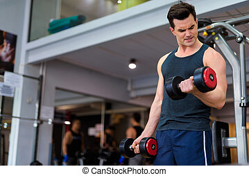 Young handsome man exercising with dumbbells at the gym