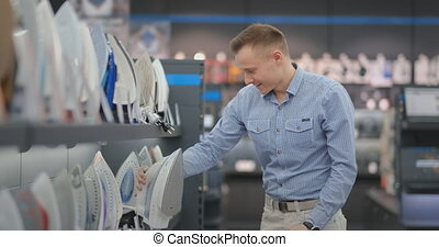 Young handsome man exploring iron to buy in a store of...