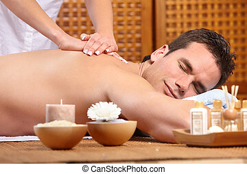 massage - young handsome man getting a massage. Spa