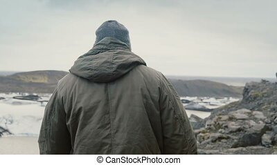 Young handsome man hiking in the mountains near the Vatnajokull ice lagoon, looking on glaciers in Iceland.