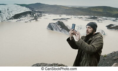Young handsome man hiking, taking photo of Vatnajokull ice...