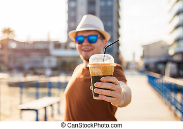 Young handsome man holding cup of take-out coffee in the city