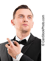 Young handsome man in a suit using a perfume
