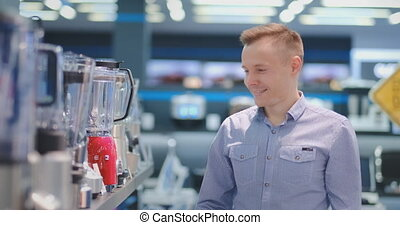 Young handsome man in appliances store chooses blender for...