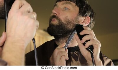 Young Handsome man in beauty saloon working on his beard and styling with comb and hairclipper.