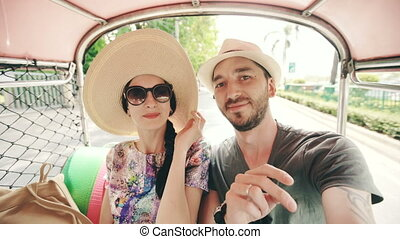 Young handsome man in hat with his girlfriend ride on traditional thai bus  taking selfie on smartphone. Couple travel Thailand during their honeymoon