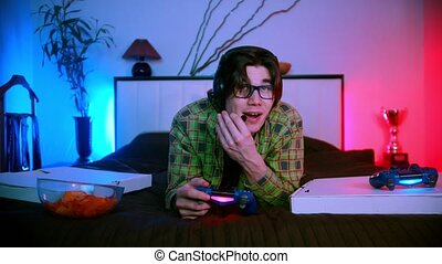 Young handsome man in headphones lying on the bed playing video game online - talking in the mic. Mid shot