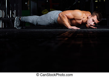young handsome man in sportswear doing push-up at gym.