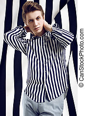 Young handsome man in striped shirt poses on black and white background