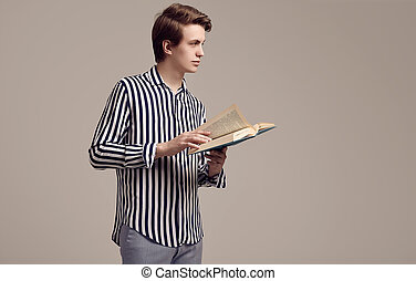 Young handsome man in striped shirt reading a book on gray background