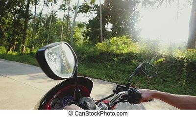 Young handsome man in sunglasses driving motorbike on...