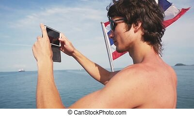 Young handsome man in sunglasses is taking photo next to...