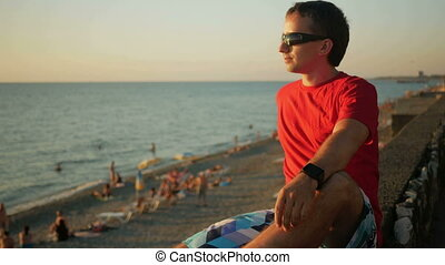 Young handsome man in sunglasses relaxing near the sea beach at sunset. He admires the sunset and water. After turning his head and looking at the camera