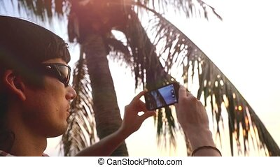 Young handsome man in sunglasses sits on a palm tree on a background of beautiful sunset takes picture with nobile phone, slow motion. 1920x1080