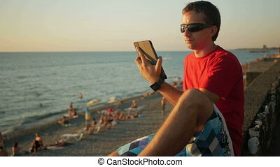 Young handsome man in sunglasses relaxing near the sea beach with tablet computer. He checks messages on social networks at sunset.
