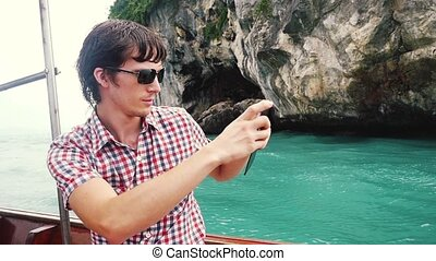 Young handsome man in sunglasses takes photo with phone in boat travel against rocky island in azure bay. slow motion. 1920x1080