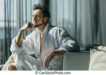 Young, handsome man in the morning thinking while sitting in a robe