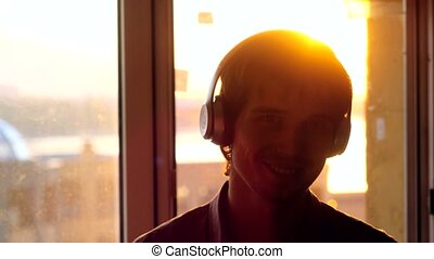 Young handsome man listening to music from a smart phone with headphones on the sunset city background. 3840x2160