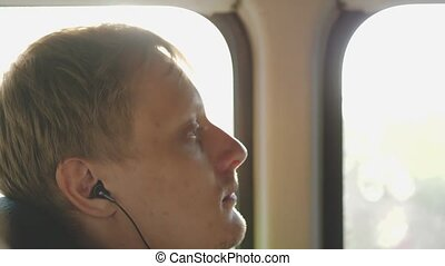 Young handsome man listening to music while rides on bus. slow motion.