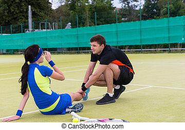 Young handsome man massaging woman's injured leg after tennis match