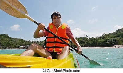 Young handsome man paddling on kayak boat in the sea. slow...
