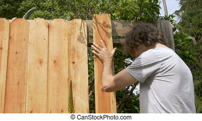 Young handsome man placing a new wooden board while...