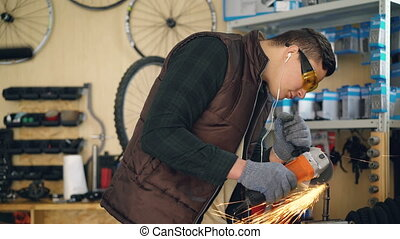 Young handsome man professional repairman in safety glasses is working with electric circular saw, sawing small metal spare part and listening to music in his workplace.