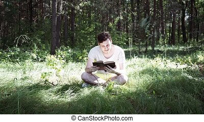 Young handsome man reading book in open space - Man reading...