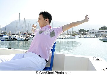 Young handsome man relaxed on his boat