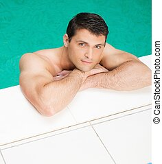 Young handsome man relaxing in swimming pool