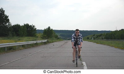 Young handsome man riding at vintage bicycle in the country road. Sporty guy cycling at the track. Male cyclist riding fixed gear bike at highway. Healthy active lifestyle Slow motion Front view