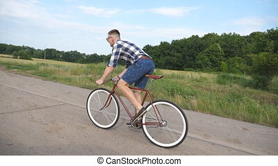 Young handsome man riding at vintage bicycle in the country road. Sporty guy cycling at the rural trail. Male cyclist riding fixed gear bike at highway. Healthy active lifestyle Slow motion