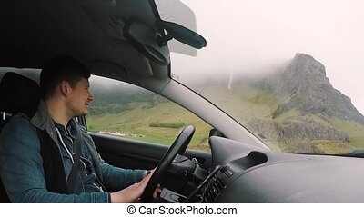 Young handsome man riding the car through the beautiful road...
