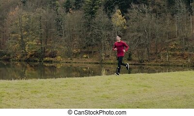 Young handsome man running in autumn nature. - Young...
