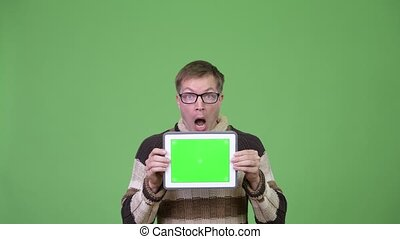 Young handsome man showing digital tablet and looking shocked