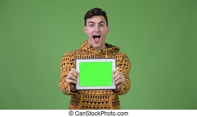 Young handsome man showing digital tablet and looking surprised