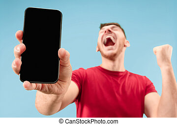 Young handsome man showing smartphone screen isolated on blue background in shock with a surprise face