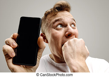 Young handsome man showing smartphone screen isolated on gray background in shock with a surprise face