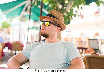 Young handsome man sitting in a street cafe.