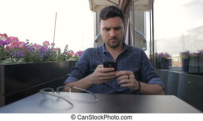 Young handsome man sitting in cafe with phone