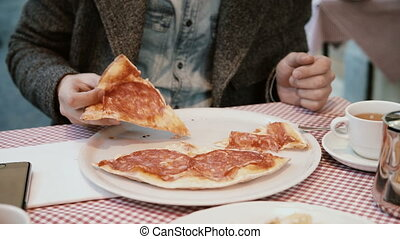 Young handsome man sitting in Italian restaurant and eating pizza. Hungry male enjoying the appetite food.
