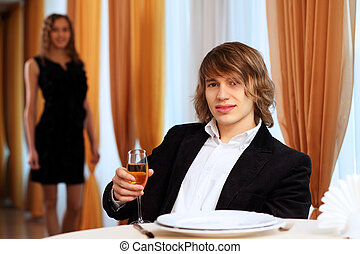 Young handsome man sitting in restaurant