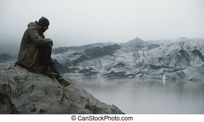Young handsome man sitting on the rock and looking on glaciers. Tourist exploring ice lagoon in Iceland alone.