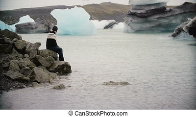 Young handsome man sitting on the rock in ice lagoon and enjoying the view. Male exploring the Iceland alone.