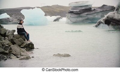 Young handsome man sitting on the rock in Jokulsalon ice...
