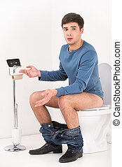 Young handsome man sitting on toilet. guy without toilet paper upset and made helpless gesture