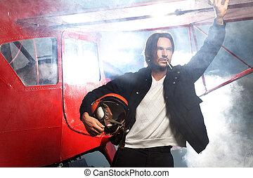 Young handsome man smoking cigarette next to aeroplane