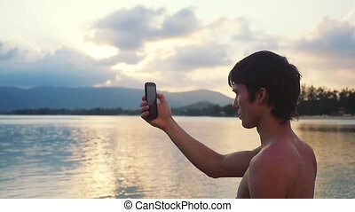 Young handsome man standing on beach taking photo with smart...