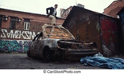 Young handsome man standing on roof of crashed car pushes hood cover with foot