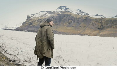 Young handsome man standing on the mountain and looking on...